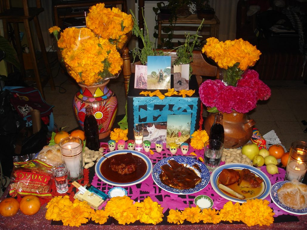 A Day of Dead altar with offerings of food and drink and candles and sugar skulls.