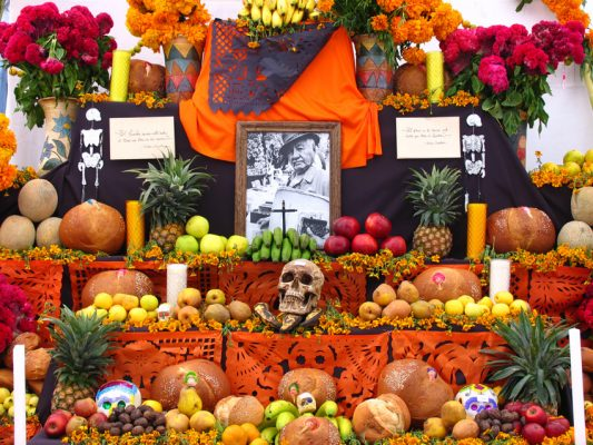 A day of the dead altar adorned with skulls, skeletons, candles, fruit, cut paper and bread.
