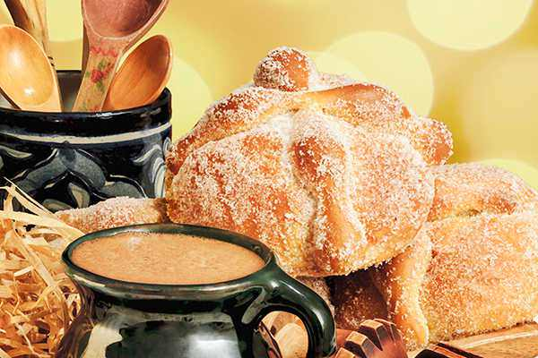 A cup of hot chocolate and a round loaf of sugared bread (pan de muerto)