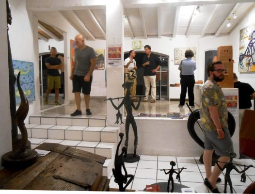 People observing paintings and sculptures in an art gallery in Puerto Vallarta Mexico.