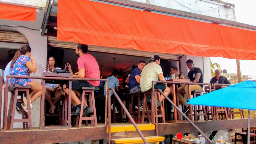 People seated around tables on the deck of el solar bar