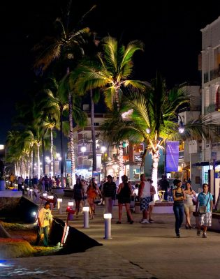People walking on the malecon at night in Puerto Vallarta Mexico.