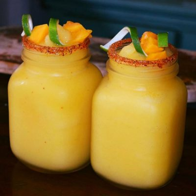 Two glasses of mango margaritas with fresh fruit on top.