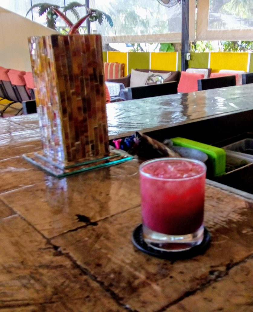 a colorful blackberry cocktail on the bar of the twisted palms bar.