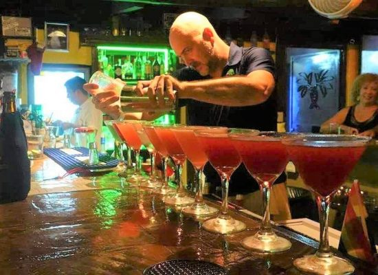 Bartender mixing a row of colorful martinis.