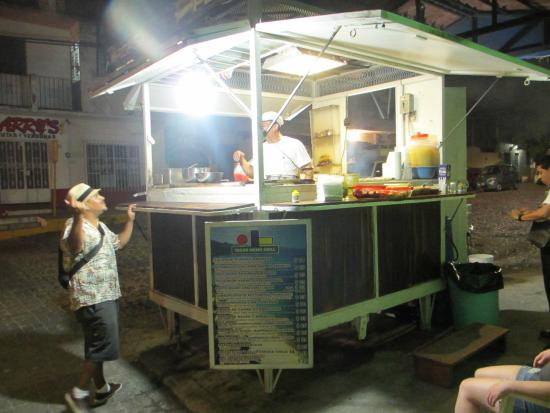 A man ordering food at a street taco stand in Puerto Vallarta Mexico.