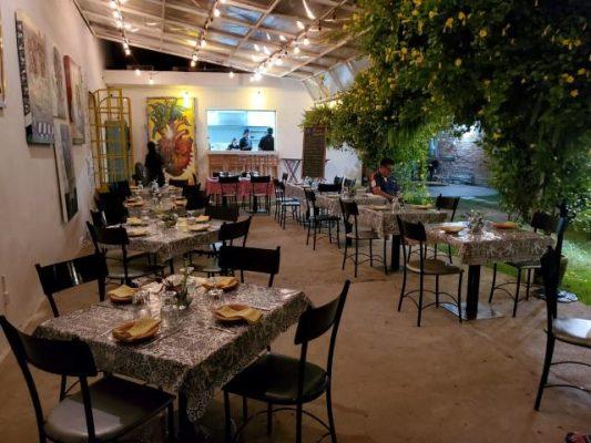 Tables on a garden patio in restaurant Barrio bistro in Puerto Vallarta