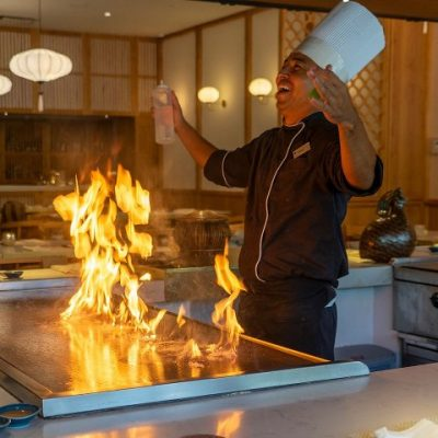 chef celebrates over a flaming grill