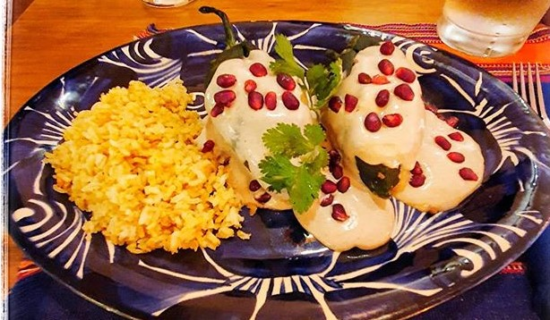 Two stuffed chiles en nogado sauce and rice on a blue plate.