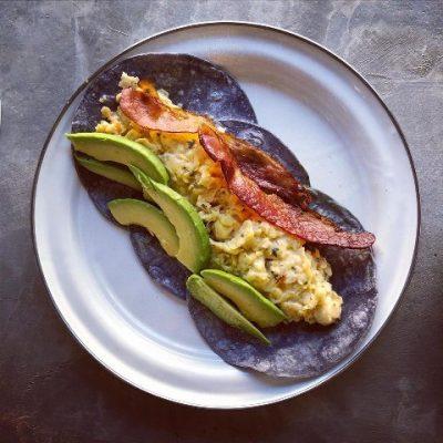 scrambled eggs, avacado slices and bacon on three blue corn tortillas.