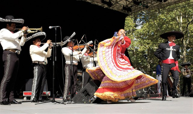 Mariachi musicians performing with a folkloric dancer on stage.