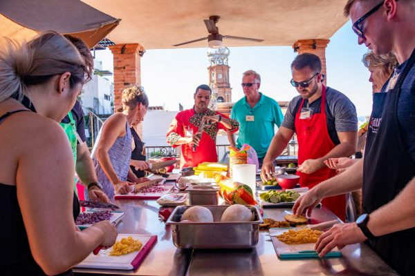 Chef Julio Castellon instructs his students around a table in a cooking glass at Gaby's in Puerto Vallarta.