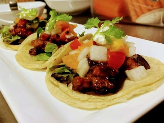 Three tacos of oxtail on a plate.