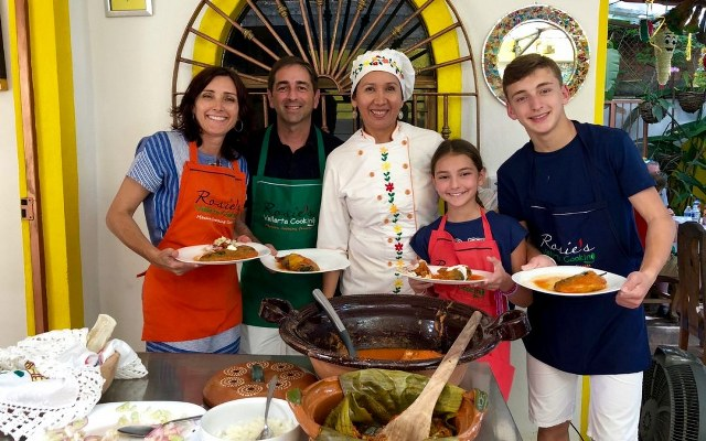 A family poses with chef Rosie, with the plates they prepared in her cooking class in Puerto Vallarta.