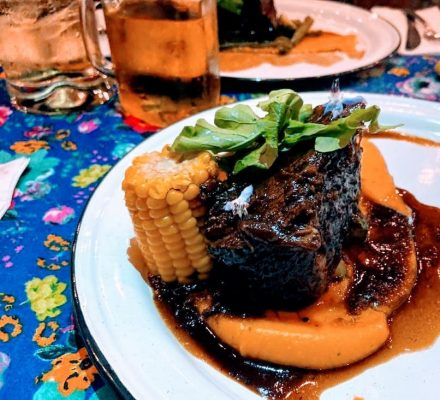 a plate with short rib and corn on the cob.