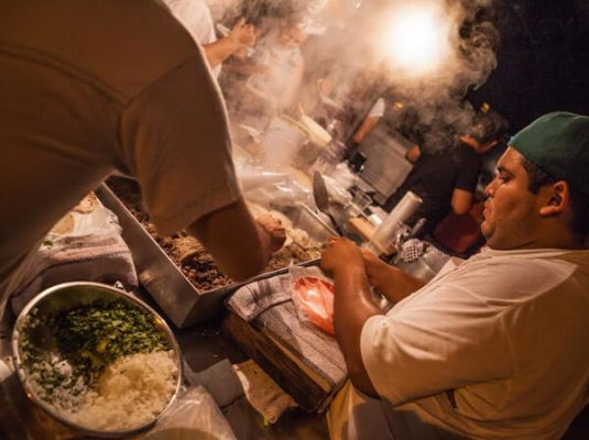 A cook prepares a taco, at a street stand,  at night in Puerto Vallarta.