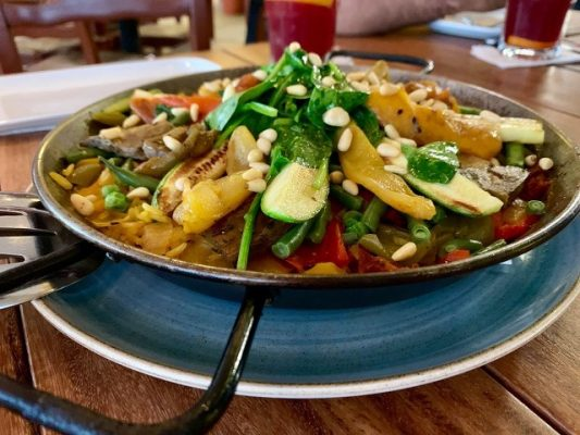 seafood and vegetables in a bowl o a blue plate