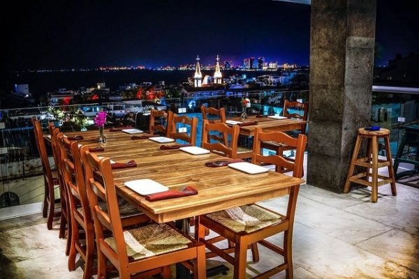 dining table with a nighttime view of church steeples and the skyline of Puerto Vallarta
