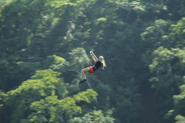 a young girl flying through the jungle on a zip line in Puerto Vallarta Mexico.