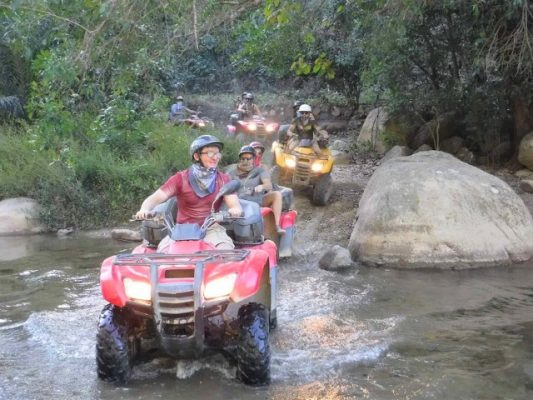 ATV  tour crossing a river in Puerto Vallarta Mexico