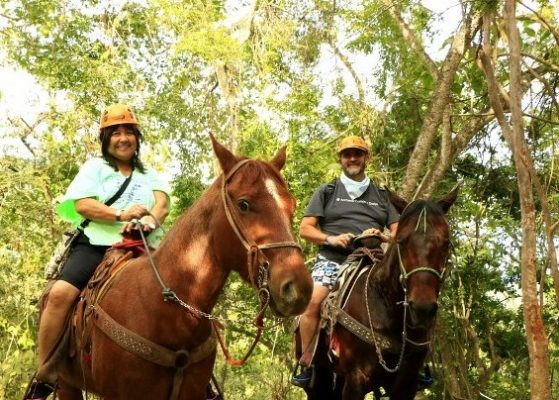 a woman and man on horses in the jungle of Puerto Vallarta Mexico