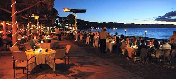 diners gathered around candle lit tables on Los Muertos Beach at La Palapa Restaurant in Puerto Vallarta