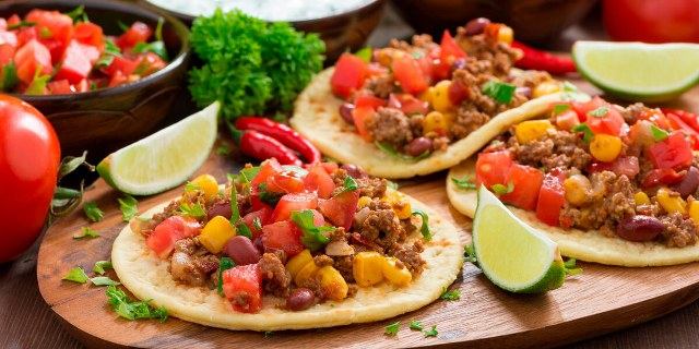 three mexican tacos with limes