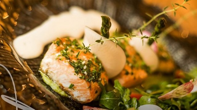 a filet of salmon with herbs and a white sauce