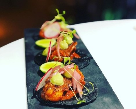 gourmet tacos of octopus on blue tortillas with lime and radish