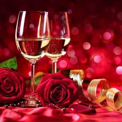two glasses of white wine with red roses infront