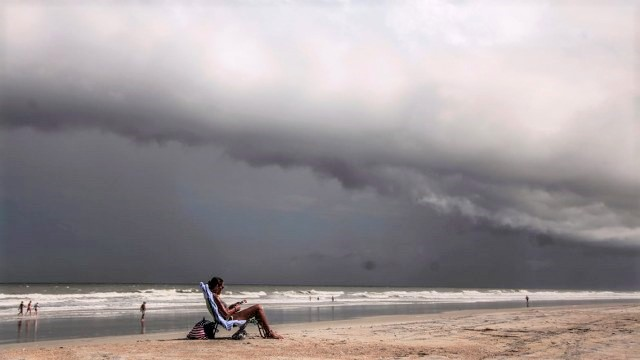 Ominous clouds form on the bay, while a beach goer is sitting reading a book.