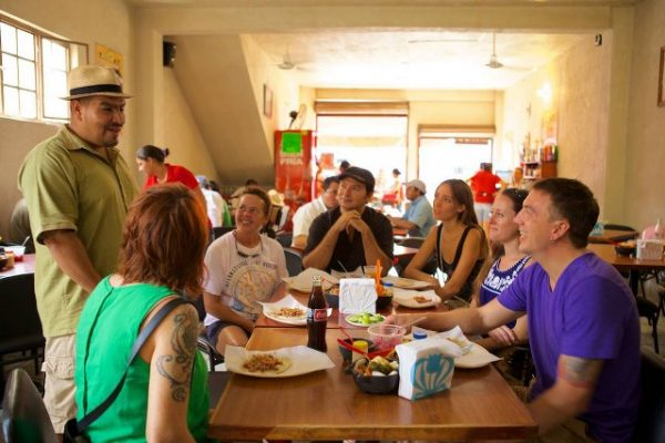 A food tour guide, from Vallarta Food ours,  explains Mexican Cuisine to tourists in Puerto Vallarta.