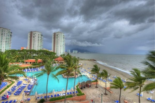 Ominous dark clouds over a hotel pool and beach in Puerto Vallarta.